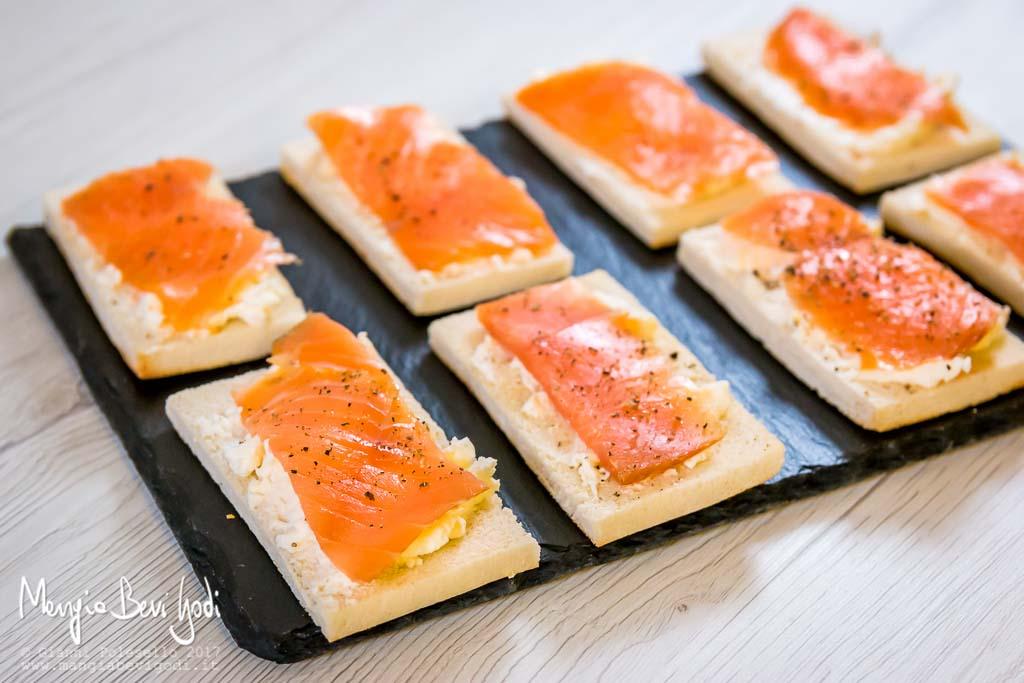 Tartine al salmone servite su piatto di ardesia