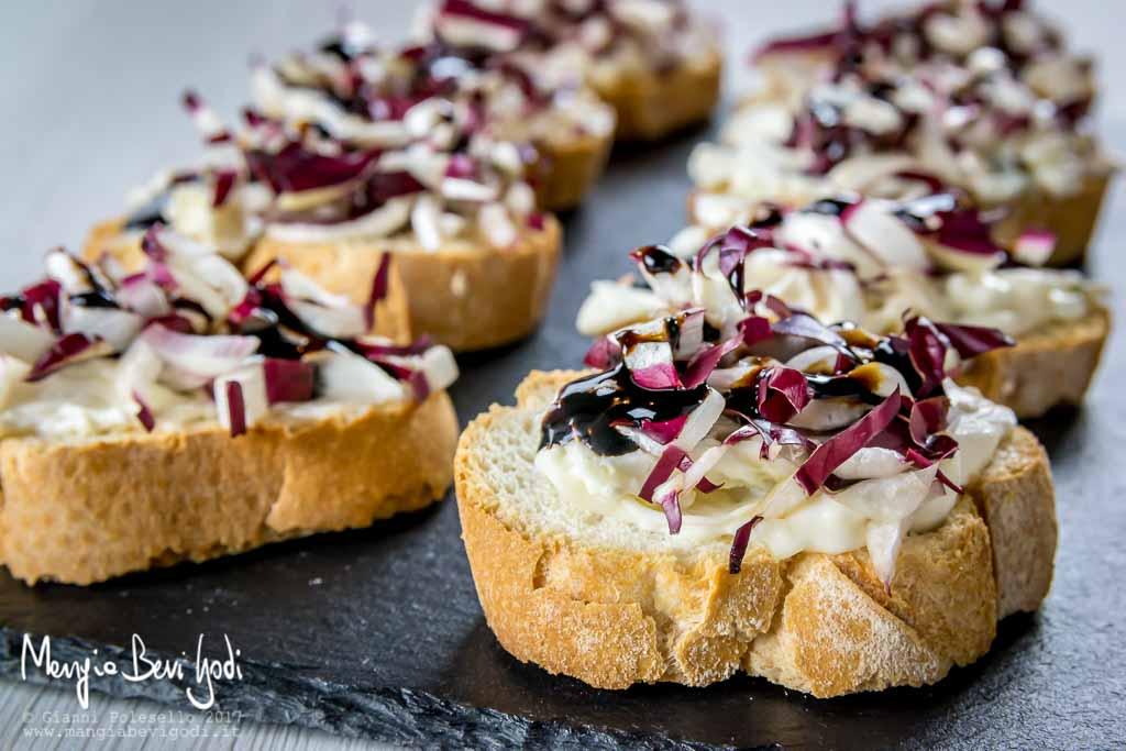 Crostini con radicchio di treviso e crema di gorgonzola e mascarpone, disposti su piatto di ardesia