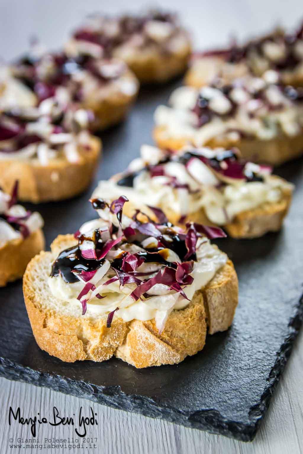 Crostini con radicchio di treviso e crema di gorgonzola e mascarpone, serviti su vassoio di ardesia