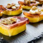 Antipasto di polenta, speck, provola e funghi sopra piatto di ardesia