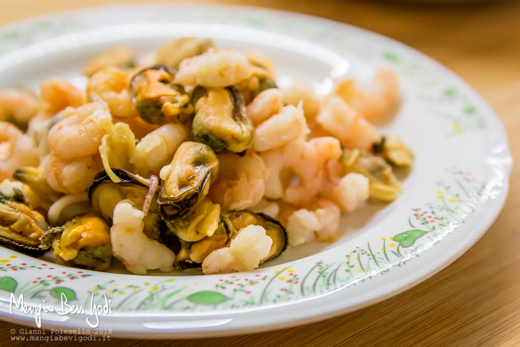 Frutti di mare (cozze, vongole, gamberetti) disposti sopra un piatto bianco