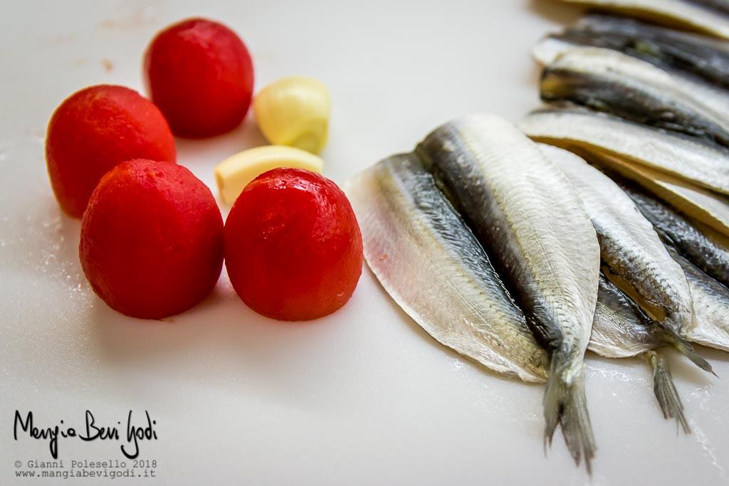 Pomodorini senza buccia, aglio e alici aperte a libro su tagliere bianco