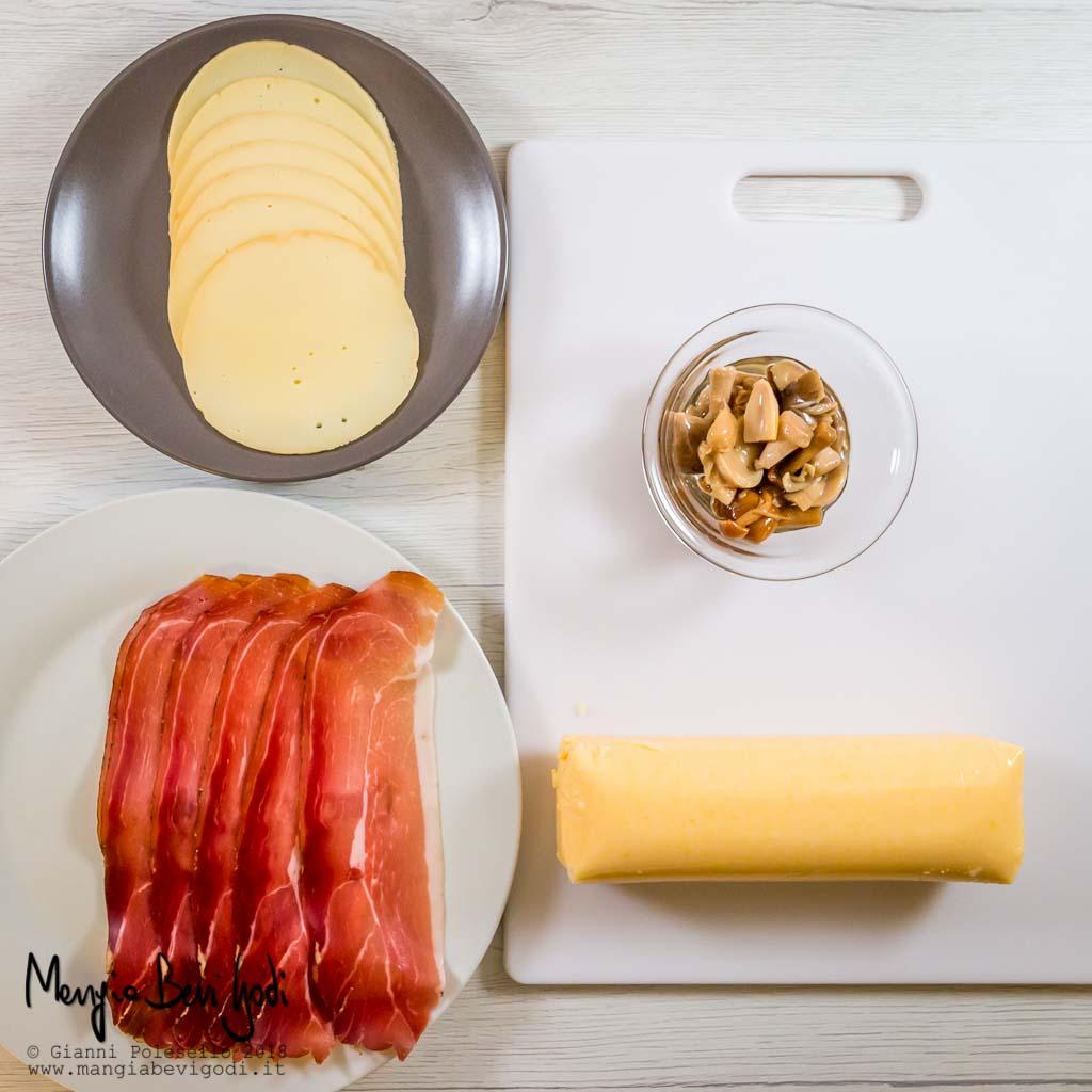 Gli ingredienti: polenta gialla pronta sopra tagliere bianco, ciotola di vetro con funghi sott'olio, piatto bianco con fettine di speck, piatto marrone con fettine di provola