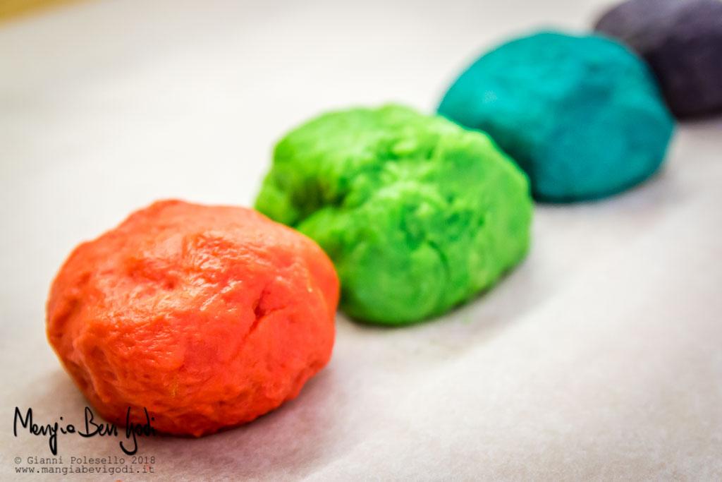 Panetti di impasto colorati. In primo piano il rosso, poi il verde, poi l'azzurro e per ultimo il viola