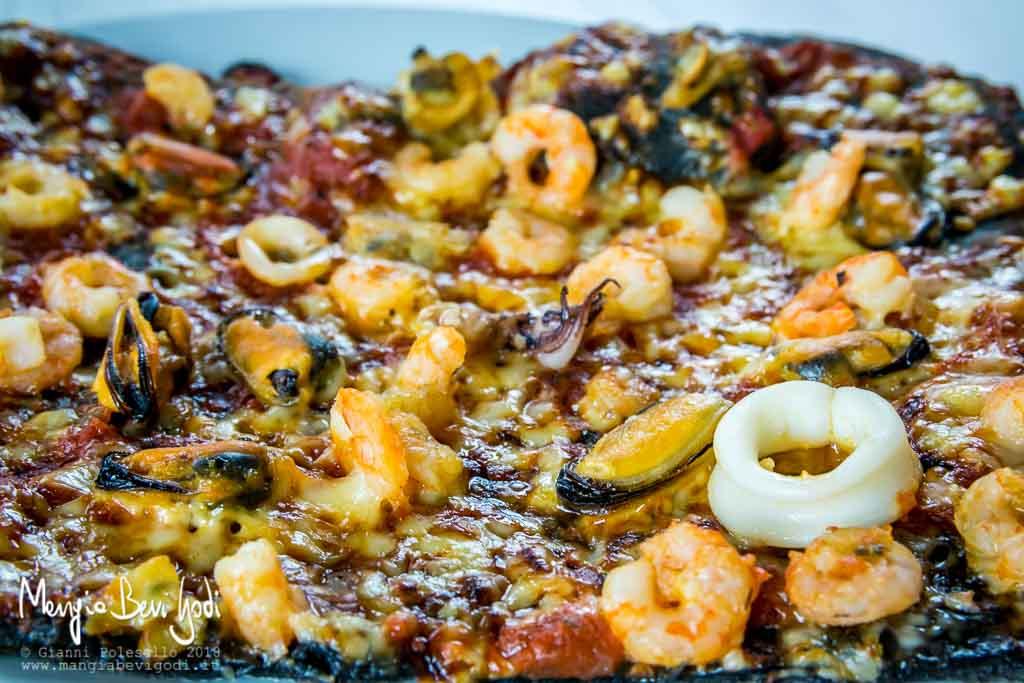 Pizza al nero di seppia con frutti di mare