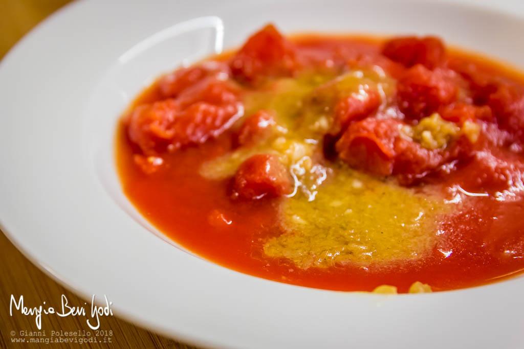 Polpa di pomodoro e fondo di cottura dei frutti di mare all'interno di un piatto fondo bianco