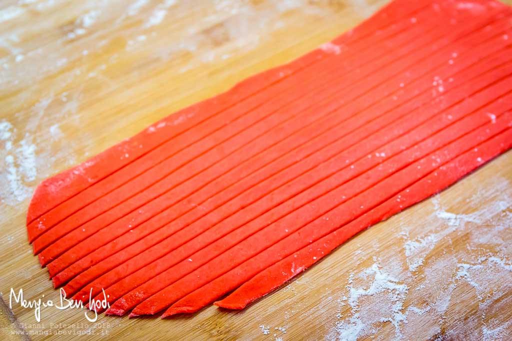 Sfoglia dolce colorata di rosso tagliata a striscioline larghe un cm