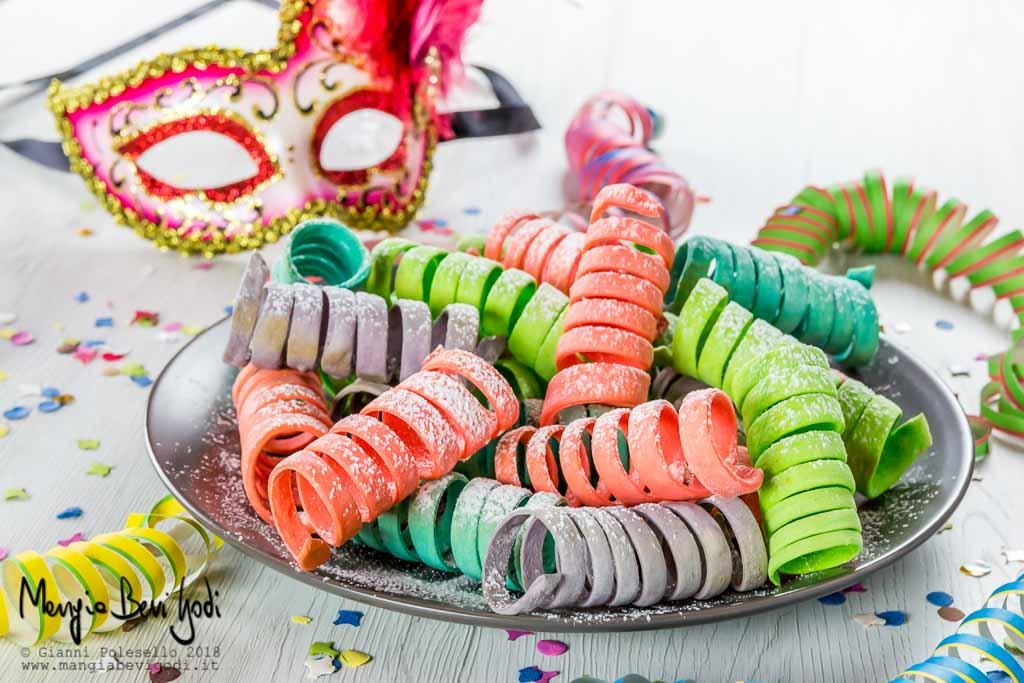 Stelle filanti dolci e colorate con maschera di Carnevale veneziana sullo sfondo