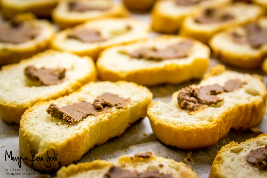 Fette di baguette tostate spalmate di pasta d'acciughe disposti su placca da forno