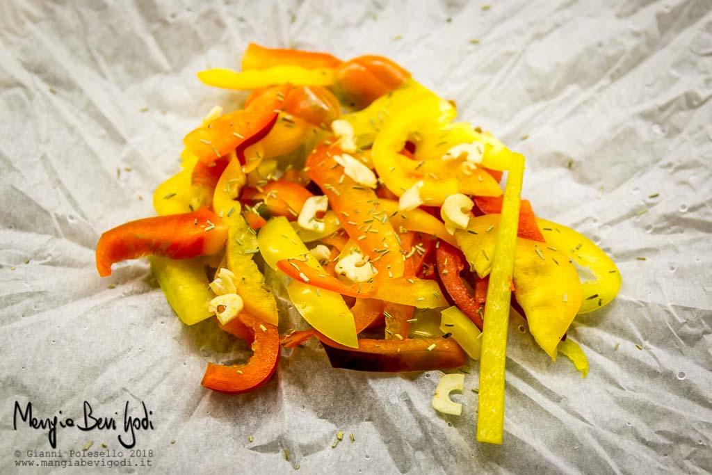 Peperoni rossi e gialli tagliati a listarelle aromatizzati con spezie posati su carta da forno stropicciata