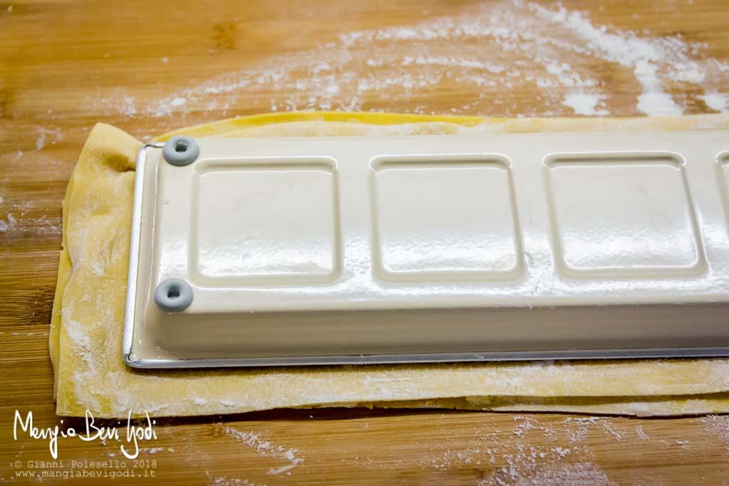 Rovesciare lo stampo per ravioli sopra una spianatoia infarinata