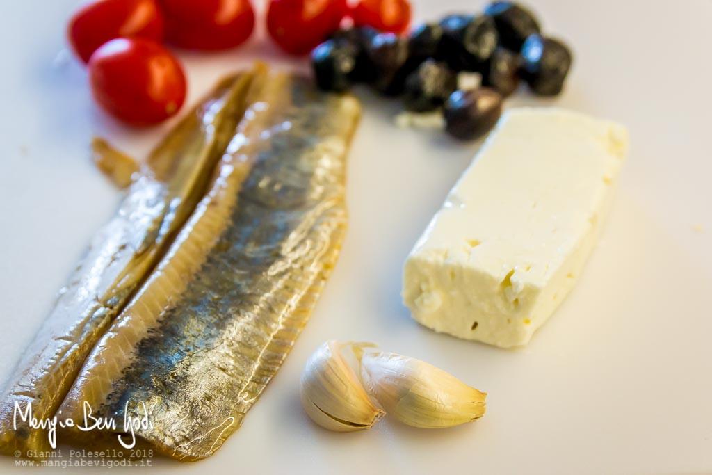 Gli ingredienti: filetti di aringa, aglio, feta greca, olive nere, pomodorini