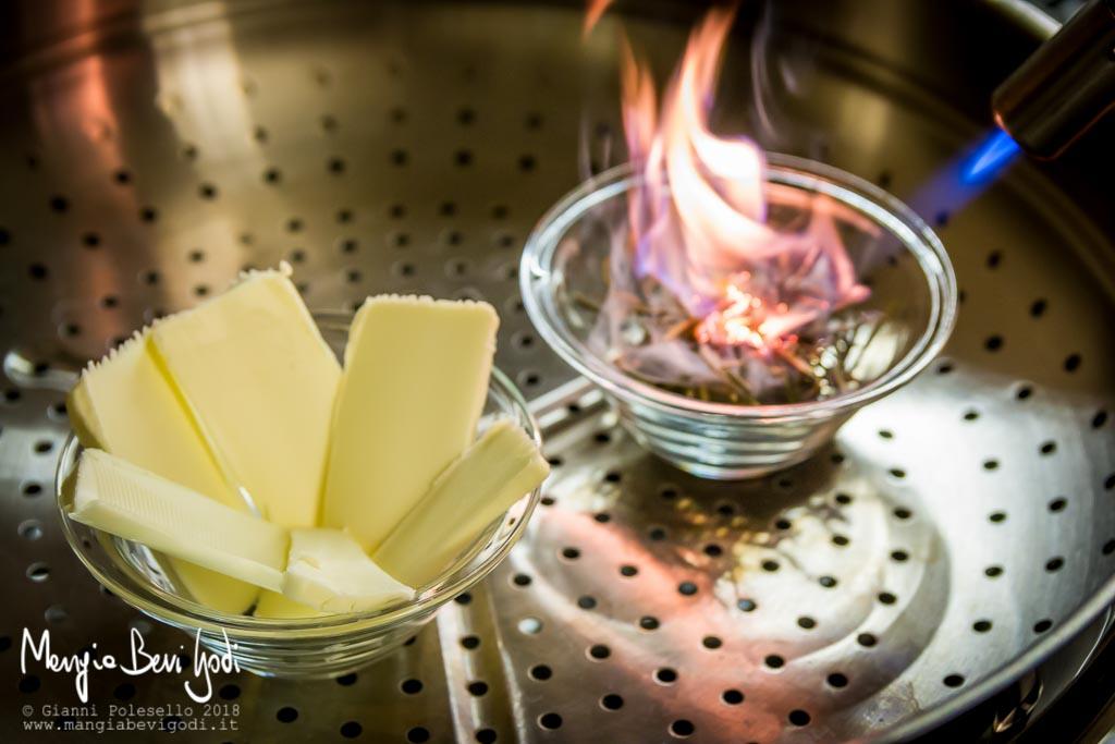 Preparazione del burro affumicato: incendiare il rosmarino essiccato con un cannello