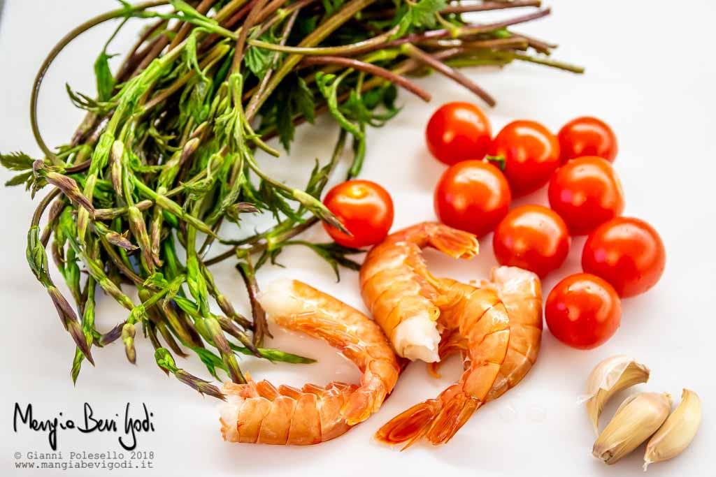 Gli ingredienti del sugo disposti su tagliere : germogli di luppolo selvatico, code di gamberoni, aglio, pomodori ciliegino