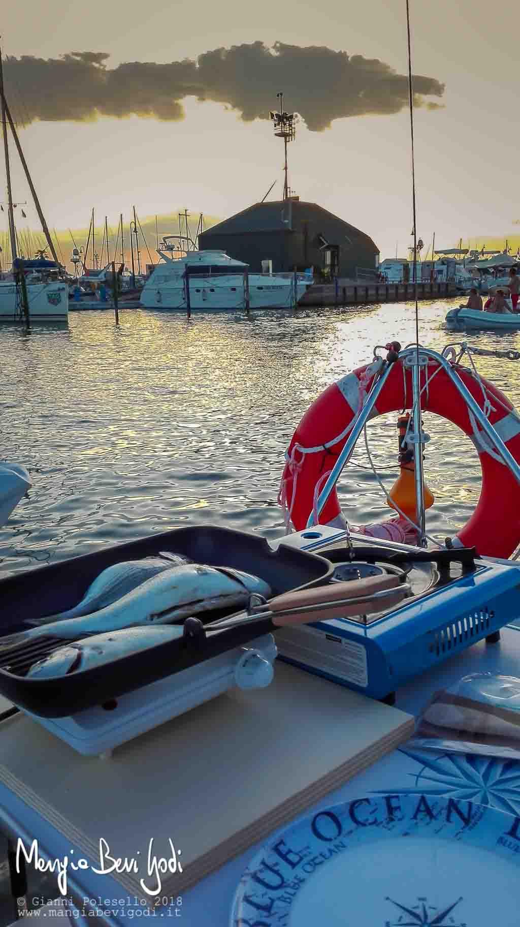 Orate alla griglia cotte in una bistecchiera nel pozzetto di una barca a vela al tramonto