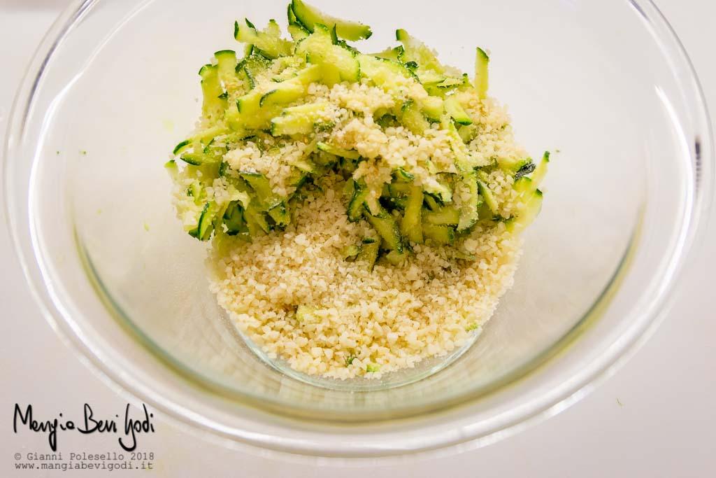 Ingredienti in una ciotola di vetro: zucchine grattugiate, aglio, prezzemolo, pangrattato, parmigiano