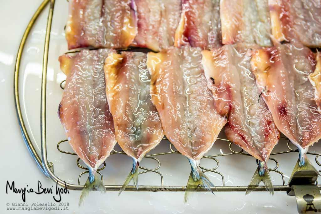 Pesce azzurro di piccola taglia disposto su una graticola di marca weber