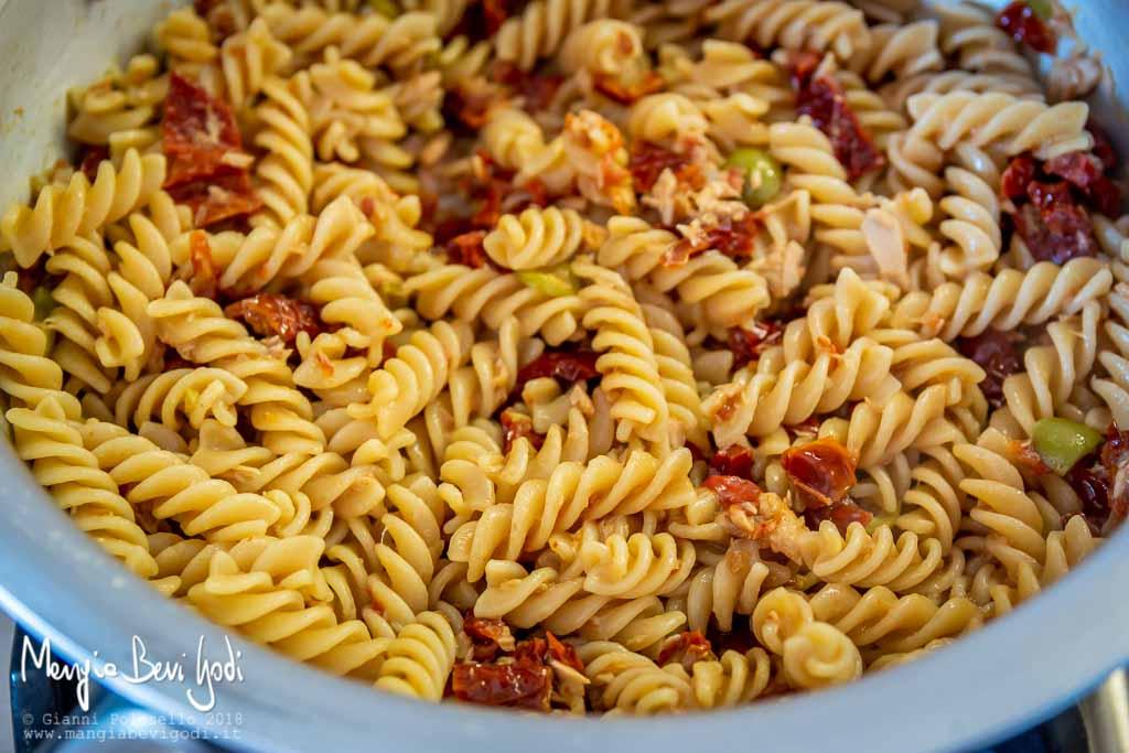 Spadellare la pasta con il sugo di pomodori secchi, tonno, olive e capperi.