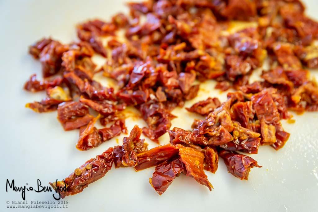 Pomodori secchi tritati al coltello sul tagliere