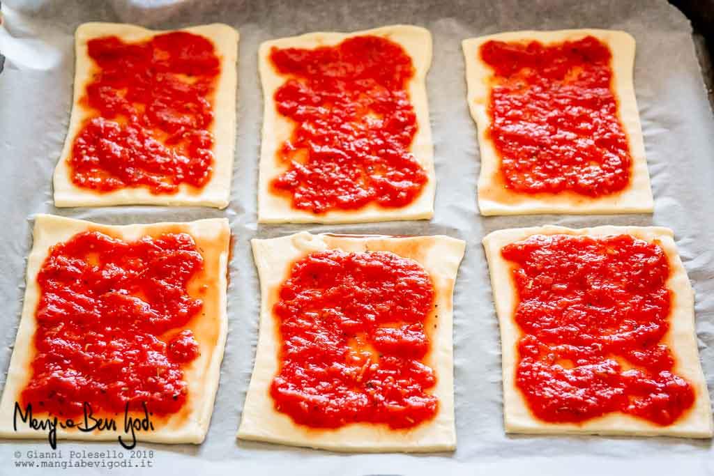 Farcire le pizzette con la polpa di pomodoro e l'origano