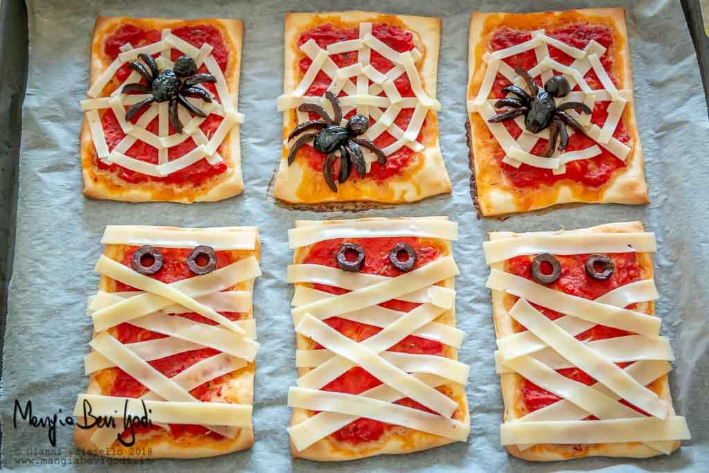 Teglia con pizzette decorate con ragni e mummie pronta da infornare