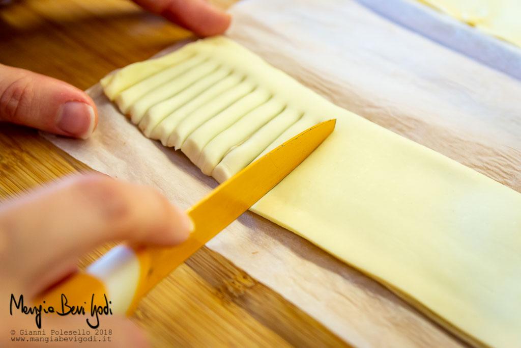Praticare dei tagli ravvicinati trasversalmente alla pasta sfoglia ripiegata