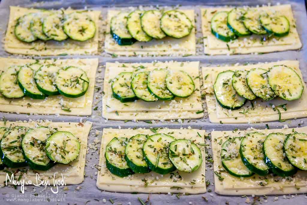 Preparazione rettangoli di pasta sfoglia con zucchine, rosmarino e formaggio.