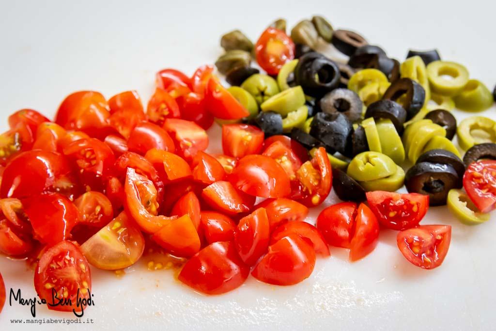 Tagliare i pomodorini, i capperi e le olive