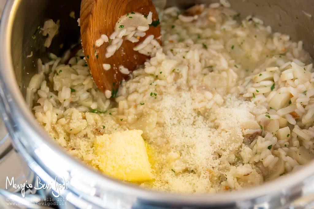 Mantecare il risotto agli asparagi e sgombro affumicato con burro, prezzemolo e parmigiano.