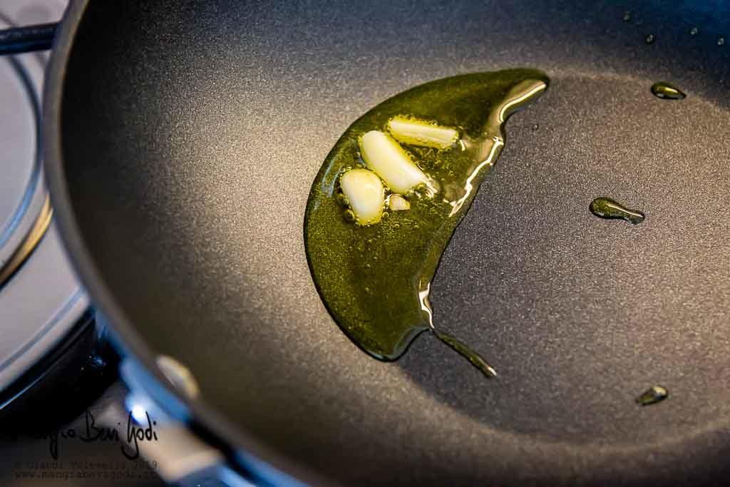 Spicchi d'aglio a soffriggere in una padella antiaderente nera