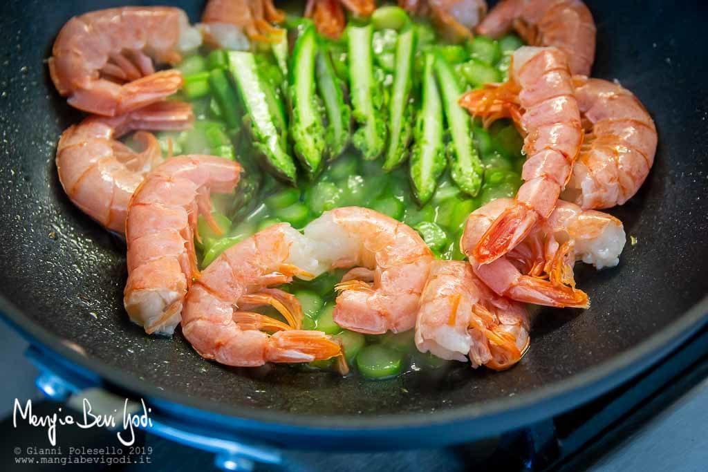 Preparazione sugo di asparagi e gamberoni in un wok antiaderente