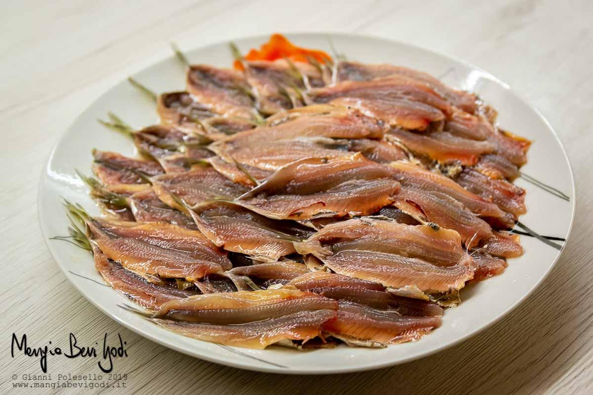 Pulire le sardine e aprirle a libro