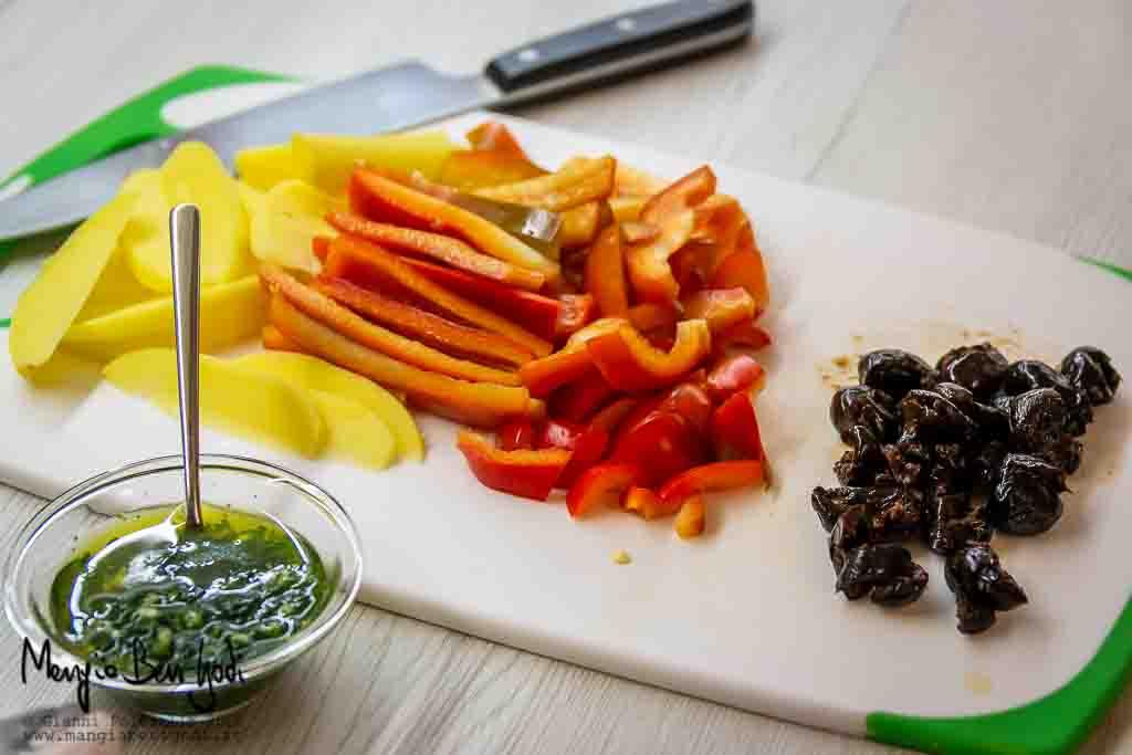 Tagliere con verdure (peperone, patata, olive) affettate e ciotola con emulsione di aglio, olio e prezzemolo
