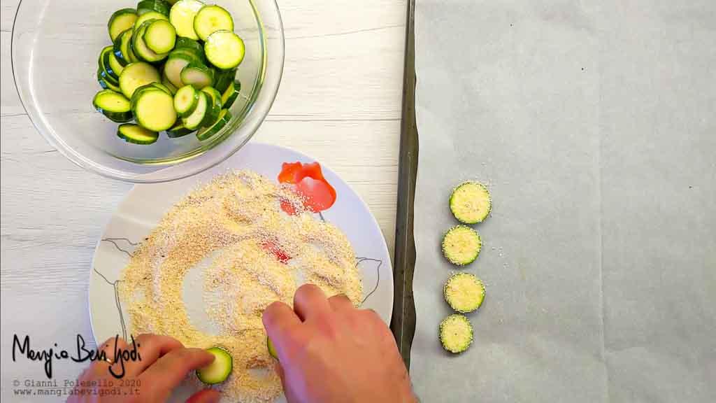 Distribuire la panatura al parmigiano sulle chips di zucchine