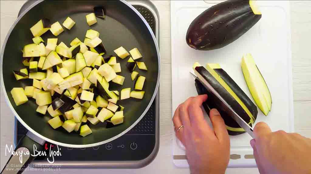 Tagliare a cubetti e cuocere le melanzane in padella