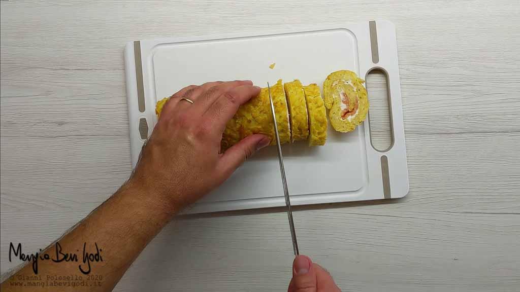 Tagliare a fette il rotolo di patate con salmone e formaggio