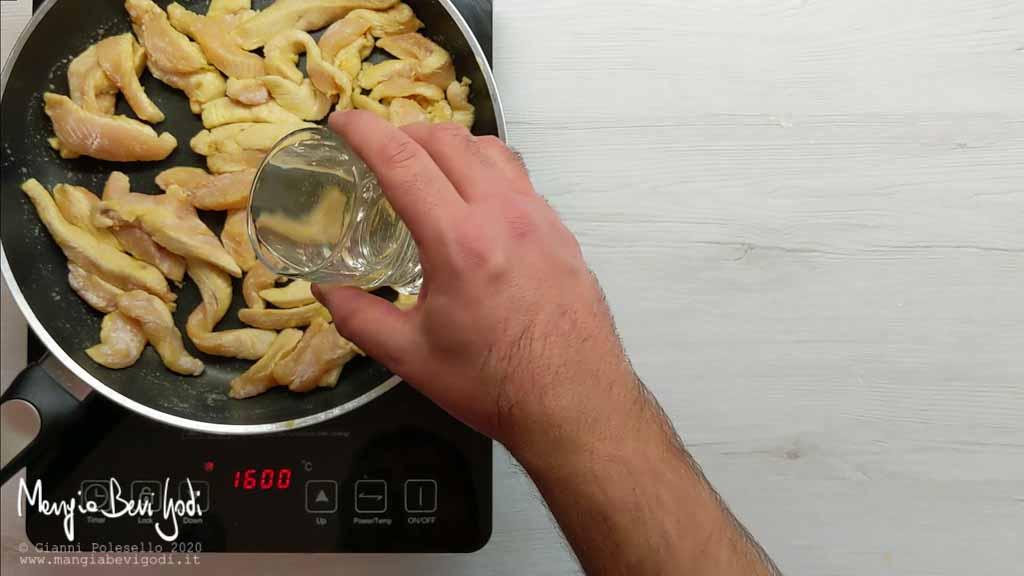 Aggiungere il vino agli straccetti di pollo