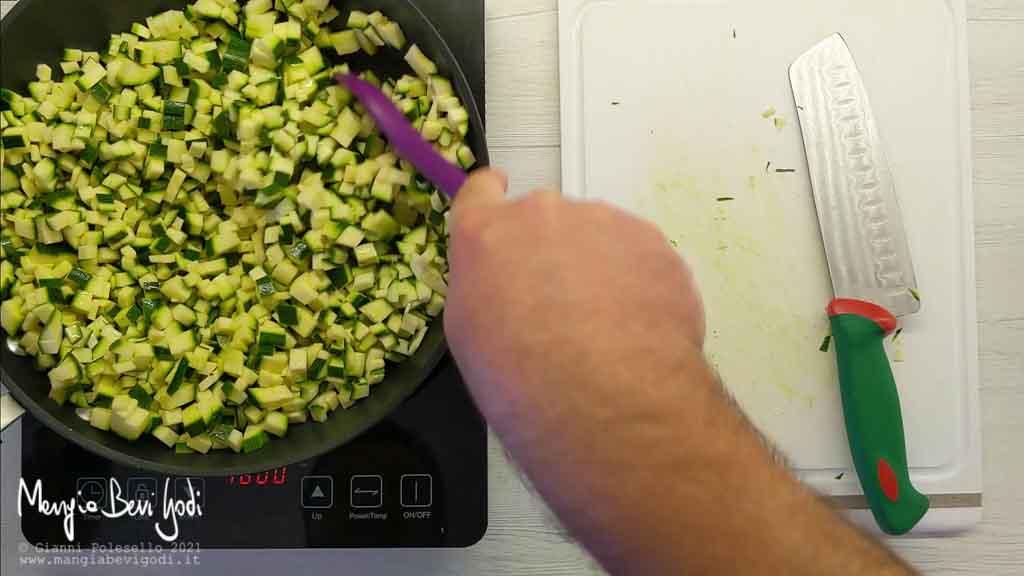 Tagliare a cubetti e cuocere le zucchine in padella