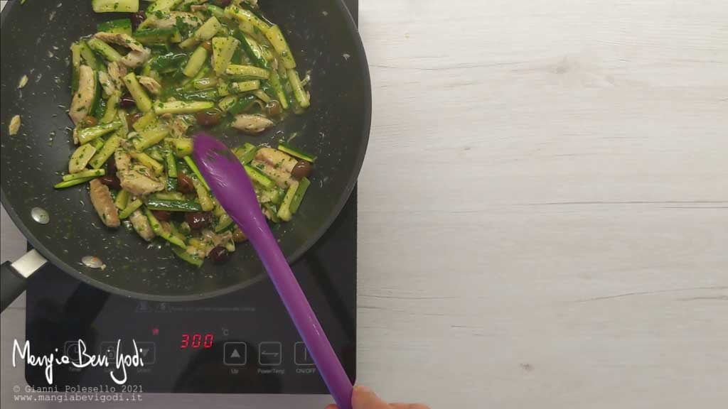 Aggiungere prezzemolo e acqua di cottura al sugo di sgombro e zucchine