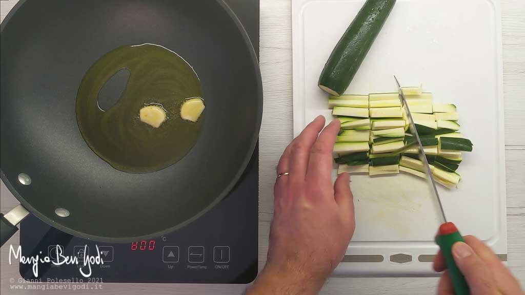 Soffriggere l'aglio e tagliare le zucchine