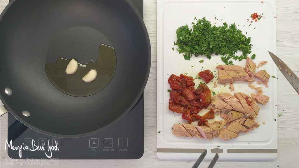 Soffriggere aglio e tagliare pomodori secchi e tonno
