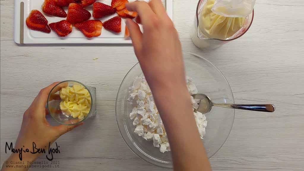 Alternare le fragole, la crema e le meringhe nel bicchiere