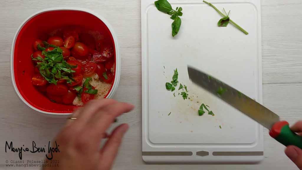 Tagliare a metà i pomodorini e tritare il basilico