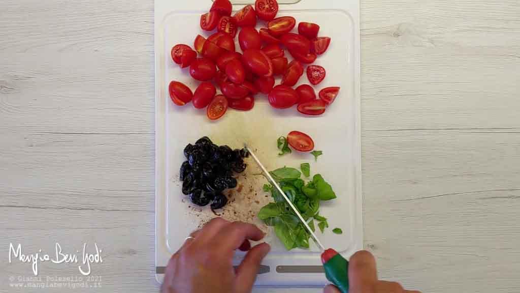 Tagliare pomodorini, basilico e olive nere