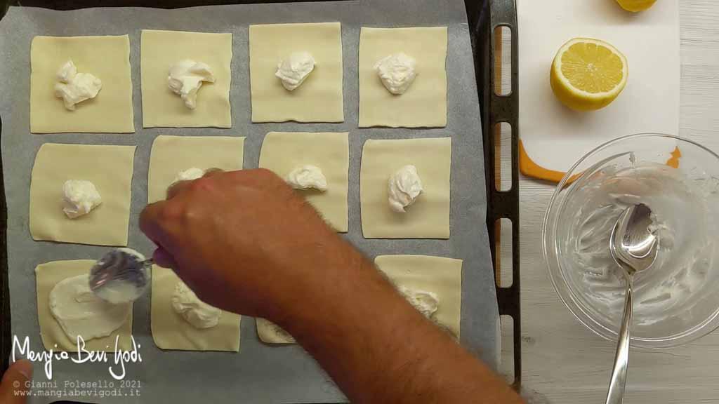 Spalmare i quadrati di pasta sfoglia con la crema