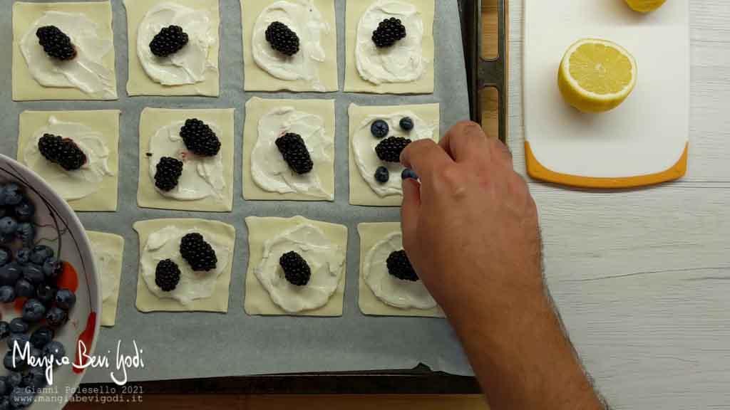 Posizionare i frutti di bosco sui quadrati di pasta sfoglia